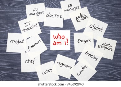 "Stickers with different professions and inscription ""Who am I?"" on gray wooden background. Profession choosing concept"