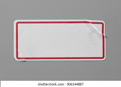 Stickers Label Close Up on Grey Background with Real Shadow. Top View of Adhesive Paper Tag with a Red Border. Copy Space for Text or Image