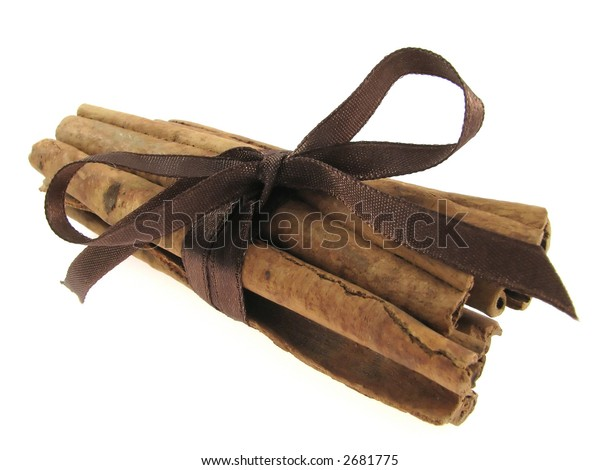 Sticks of cinnamon joined brown string on the white background