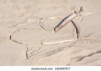 Sticks layed out in a shape of a heart pierced by an arrow on the beach sand. Love confession, honeymoon, holiday romance concept. Close-up, copy space, selective focus