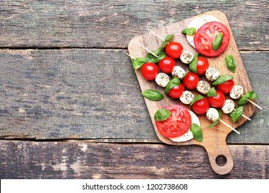 Sticks with mozzarella, tomatoes and basil leafs on wooden cutting board