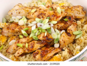 Sticky Chicken with mango couscous, garnished with spring onions and a mustard glaze