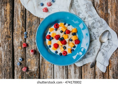Sticky mango rice with berries in a blue bowl on a rustic background