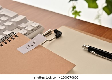 A sticky note labeled MVP is taped to the edge of a notebook on the desk.That's an acronym for Minimum Viable Product.