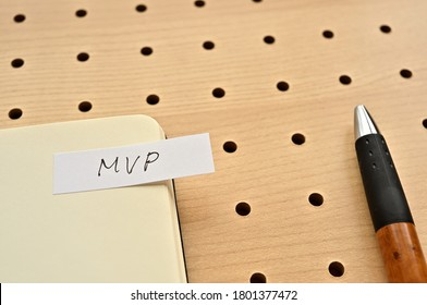 A sticky note with MVP written on the edge of an open notebook on the punching board. That's an acronym for Minimum Viable Product.