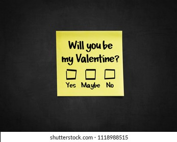 A sticky note on blackboard that says 'Will you be my Valentine?'