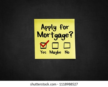 A sticky note on blackboard that says 'Apply for Mortgage?'