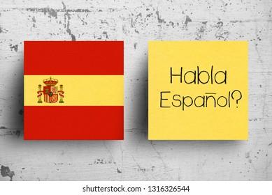 Sticky note on concrete wall.  Habla Espanol? Do You Speak Spanish?
