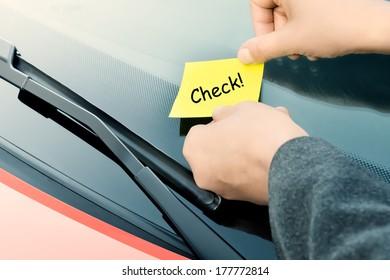 Sticky note on a windshield - Check