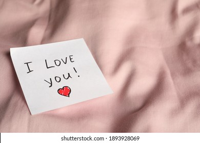 Sticky note with phrase I love you! on bed, closeup. Space for text