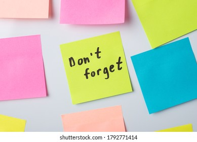 Sticky note with text Don't forget among other notes on a whiteboard in the office