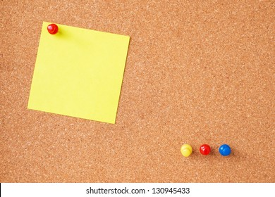 Sticky notes with thumbtacks on cork board