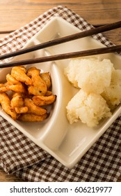 Sticky rice with fried chicken in food container on wood table.