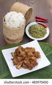 Sticky rice, fried pork with green chili dip on wood table, Thai food
