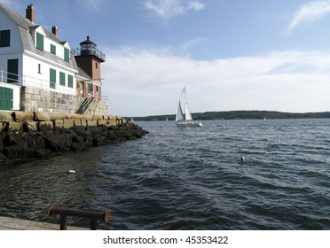 A stiff breeze pushes a beautiful sailboat around the point of Breakwater Lighthouse, Rockland Harbor, Maine.