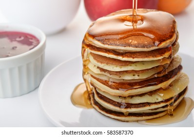 Stii life with pancakes stack pouring marple syrup