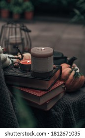 Stil life with books, candles, pumpkin, lantern and a tea pot. Autumn/Fall or Halloween concept.