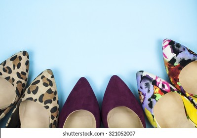 Stiletto shoes in different colors and patterns on light blue surface.