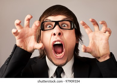 Stilish businessman screaming ang expressing anger. On a grey background