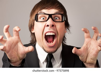 Stilish businessman screaming and expressing anger. On a gray background