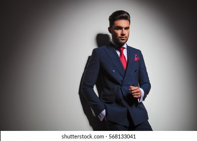 stilish man in double breasted suit standing against grey wall with copy space in studio