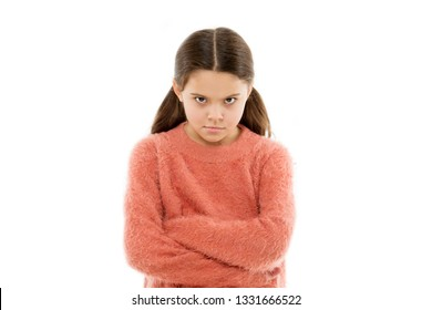 Still angry. Disagreement and stubbornness. Girl serious face offended white background. Kid little girl unhappy looks strictly. Girl folded arms on chest looks serious. Stubborn child temper.