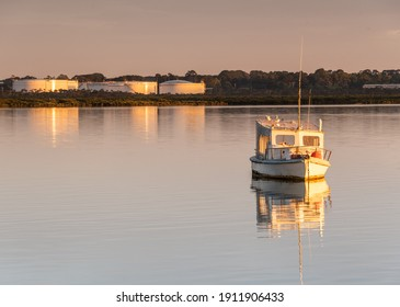 Still bay with a run-down fishing boat in the foreground.  Oil storage tanks in the background surrounded by mangrove taken at sunrise golden hour.  Taken at Hastings Victoria Australia.