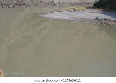 Still brown river water with sandbank
