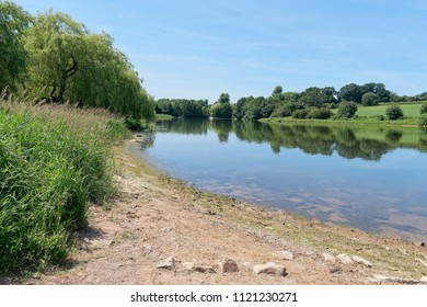 The still, calm water of Staunton Harold Reservoir, Derbyshire, reflects the surrounding countryside in its surface.