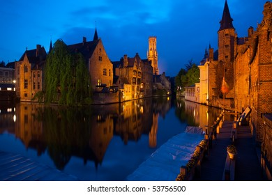 A still canal reflecting the old red brick buildings and belfry of the historic old town on Rozenhoedkaai Street at dusk blue hour in Bruges, Belgium. Horizontal copy space