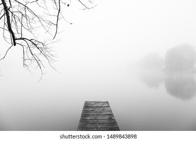 Still, the lake rests in the fog. The foreground is a walkway to the water
