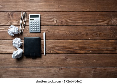 Still life of accountant workspace with office accessories. Flat lay vintage wooden desk with black leather wallet, calculator and notepad. Accounting and banking services. Finance and payment concept