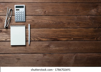 Still life of accountant workspace with office accessories. Flat lay wooden desk with elegant glasses, calculator and spiral notepad. Accounting and banking services. Finance and investment concept.