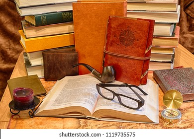 Still life of the adventurer: a book, glasses, a pipe for smoking, a leather purse, a compass, a candle on a candlestick and notebooks in a leather cover against a stack of books and ancient world map