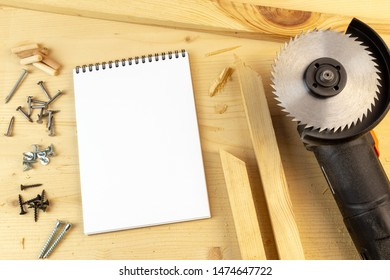 Still life of angle grinder and cut wood with some screws and a notebook arranged on a table surface. Copy space for text. Concept of project in carpentry or household and furniture diy assembly.