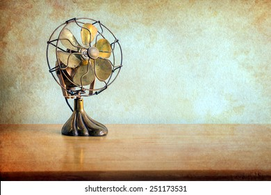 still life with antique fan on wooden table over grunge background