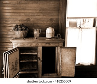 Still life of antique refrigerator with a cookie jar, pitcher, pine cones, and a window in sepia tone.