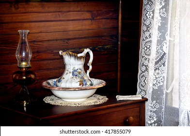 Still life of antique wash basin with a kerosene lamp and white lace curtains.