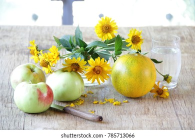 still life with apples, melon and a bouquet of yellow daisies