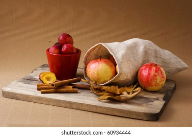 still life with apples, plums and cinnamon