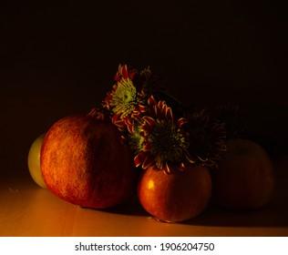 Still life of apples, pomegranates and chrysanthemums.