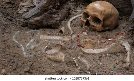 Still life of archaeological excavation with skull, bones and ancient glass beads necklace still half buried in the ground of ancient grave