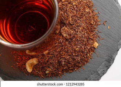 Still life, aromatic dry tea with fruits and petals, close up on with a cup of tea on white background, selective focus