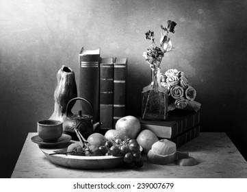 Still life art photography with books fruits roses on marble table black and white version
