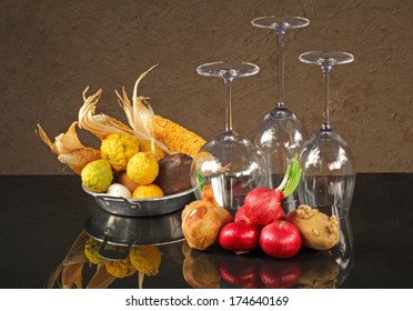 Still life art photography of mixed vegetables with up side down wine glasses