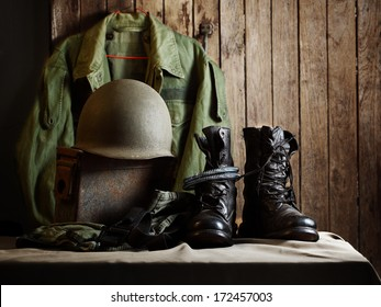 Still life art photography on vintage army concept jacket field coach helmet jungle boots and metal bullets box