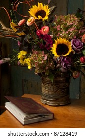 Still life with autumn flowers in a stoneware vase and gold embossed leather bound book on antique wooden table. Low key, dark background, spot lighting, and rich Old Masters colors. Vertical format.
