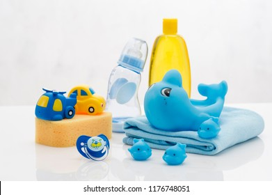 Still life with baby hygiene and bath items, shampoo bottle, essential oil, baby soap, towel, pacifier, rubber toy, shower puff