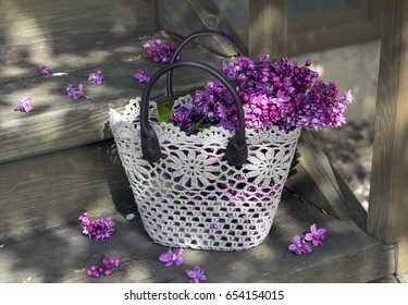 Still life with basket and branches of lilac on a wooden porch of a country house.