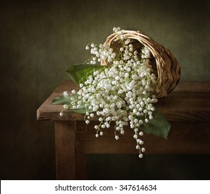 Still life with a basket full of lilies of the valley (textured for artistic effect)